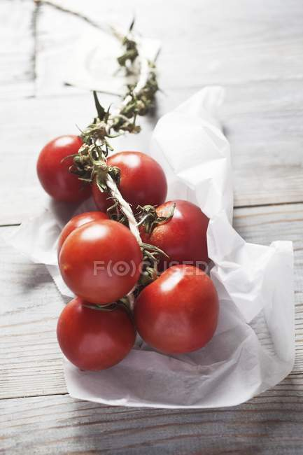 Tomatoes on vine on paper — Stock Photo