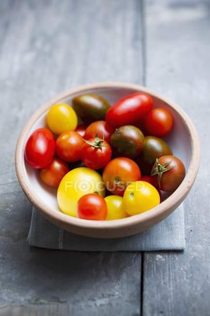 Tomates coloridos en un tazón - foto de stock