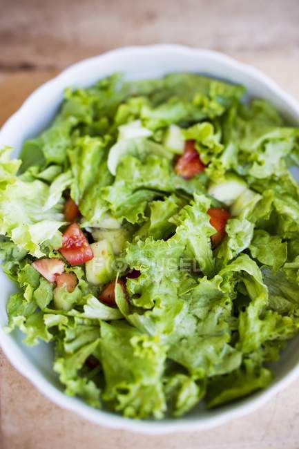 Salad leaves with cucumber, tomatoes and vinaigrette in bowl — Stock Photo