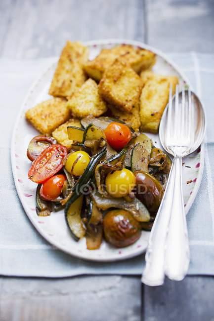 Zucchini mit Polentastücken und Tomaten auf weißem Teller mit Gabel und Löffel über dem Tisch — Stockfoto