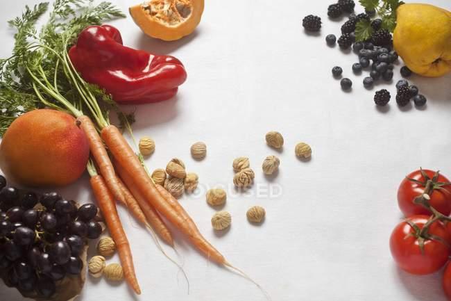 Una naturaleza muerta de verduras, frutas y castañas dulces secas que ponen sobre la superficie blanca - foto de stock