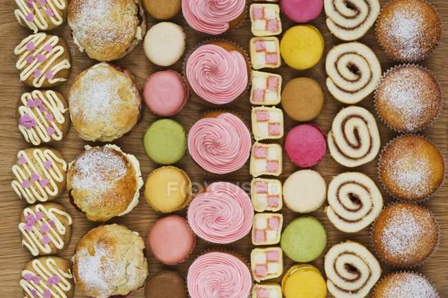 Ряды кексов, булочек и макарон — стоковое фото