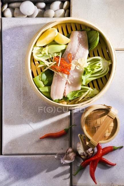 Pesce al vapore con verdure in ciotola gialla — Foto stock