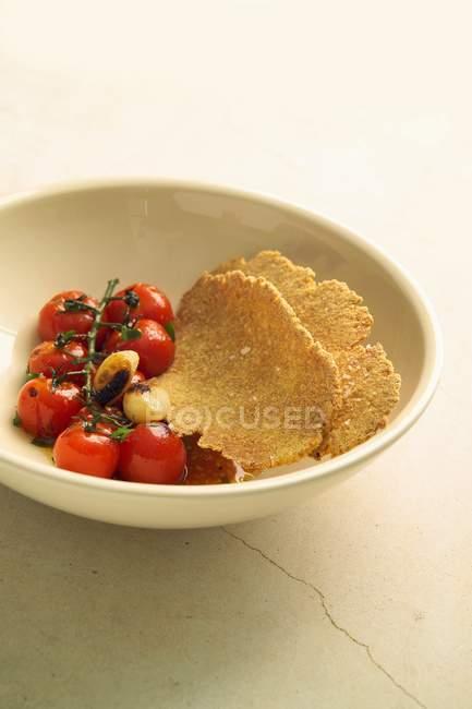Pomodori arrostiti e semolino tostato pane piatto sulla zolla bianca — Foto stock