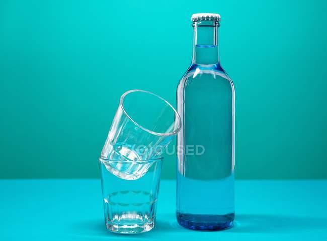 Vista del primo piano di bicchieri d'acqua con una bottiglia di acqua — Foto stock