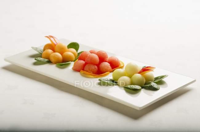 Diverse palline di melone sulla zolla bianca — Foto stock