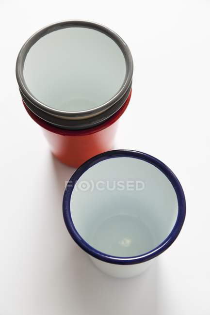 Closeup elevated view of enamel mugs on white surface — Stock Photo