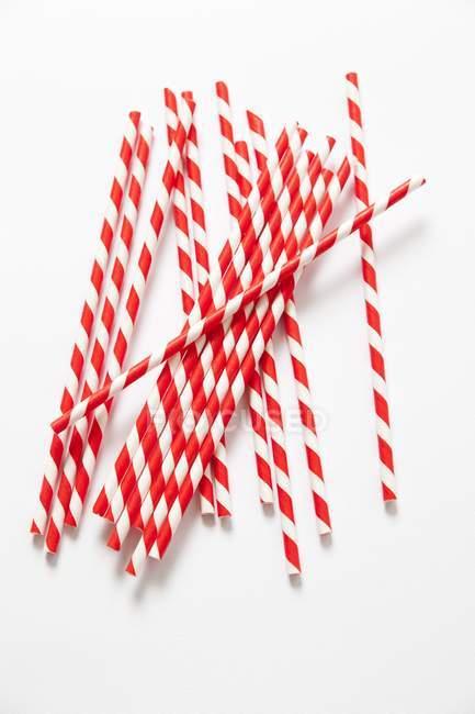 Vista superior de vermelho e branco bebendo palhas sobre uma superfície branca — Fotografia de Stock