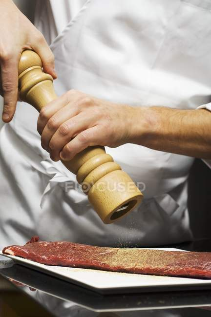 Koch, Rindfleisch mit Pfeffer würzen — Stockfoto