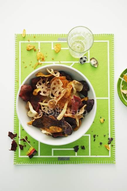 Chips de légumes racine coloré sur une plaque blanche sur la serviette comme terrain de football — Photo de stock