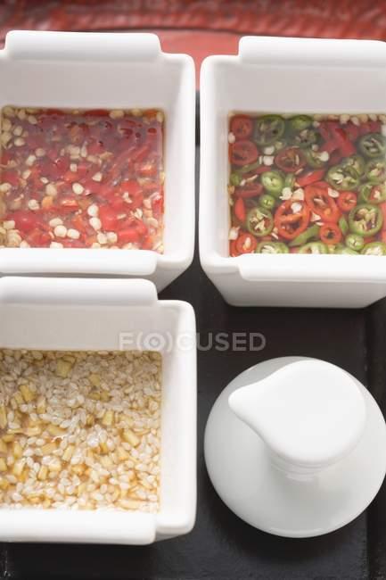 Trois sauces asiatiques épicées dans des bols blancs — Photo de stock