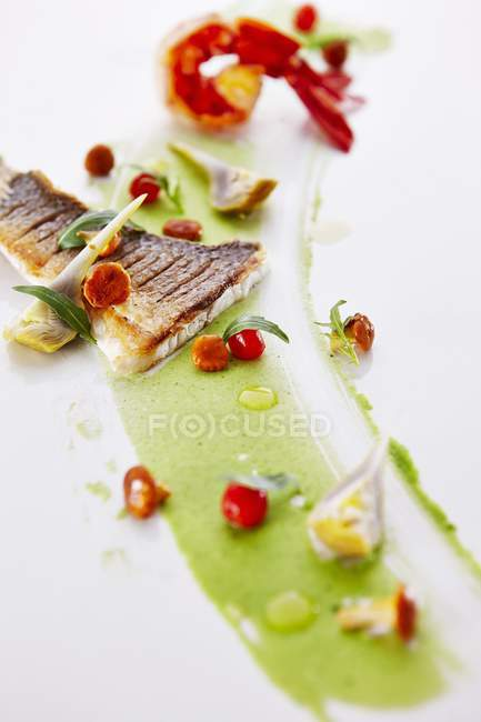 Zander and scampi in pea cream with artichokes on white background — Stock Photo