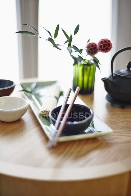 Vue de jour surélevée d'un arrangement oriental comprenant un bol, des baguettes, des nouilles et du thé — Photo de stock