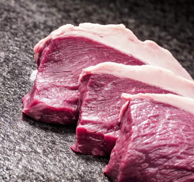 Три raw стейки — стокове фото