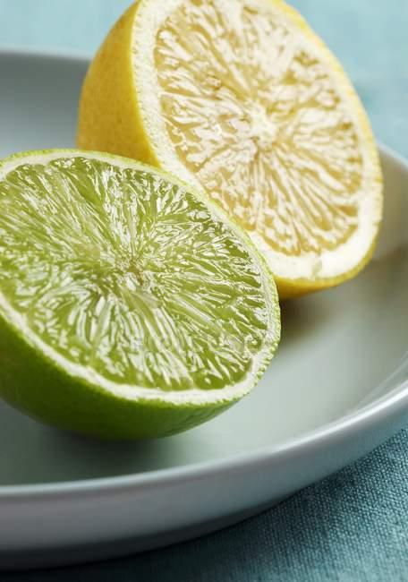 Роздвоєна лимона і вапна на тарілці — стокове фото