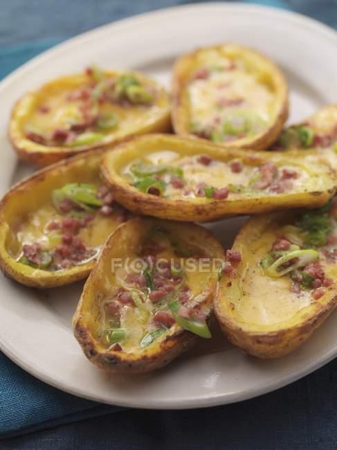 Cascas de batata assadas com bacon e cebolinhas em chapa branca — Fotografia de Stock