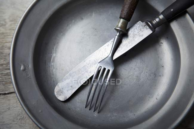 Closeup view of a tin plate with silver cutlery — Stock Photo