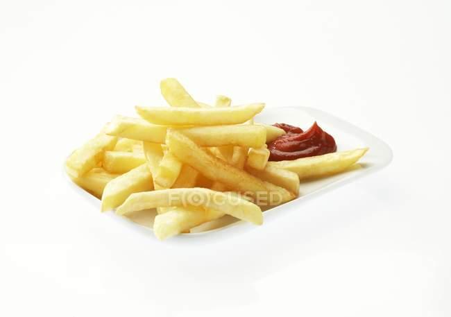 Patatas fritas con salsa de tomate en placa - foto de stock