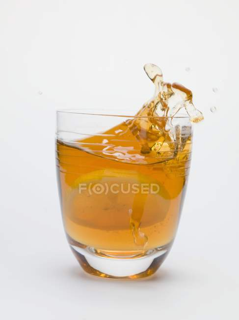 Iced tea splashing out of glass — Stock Photo