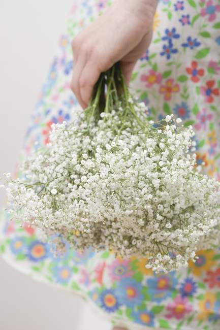 Vue recadrée de la femme en robe fleurie tenant des fleurs de Gypsophila — Photo de stock