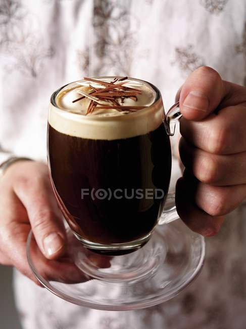 Hands holding Irish coffee — Stock Photo