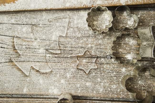 Vista de cerca de una superficie de madera enharinada con cortadores de galletas - foto de stock