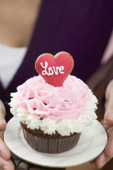 Female hand holding cupcake — Stock Photo