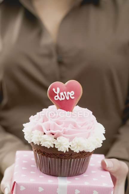 Female hand holding cupcake and gift — Stock Photo