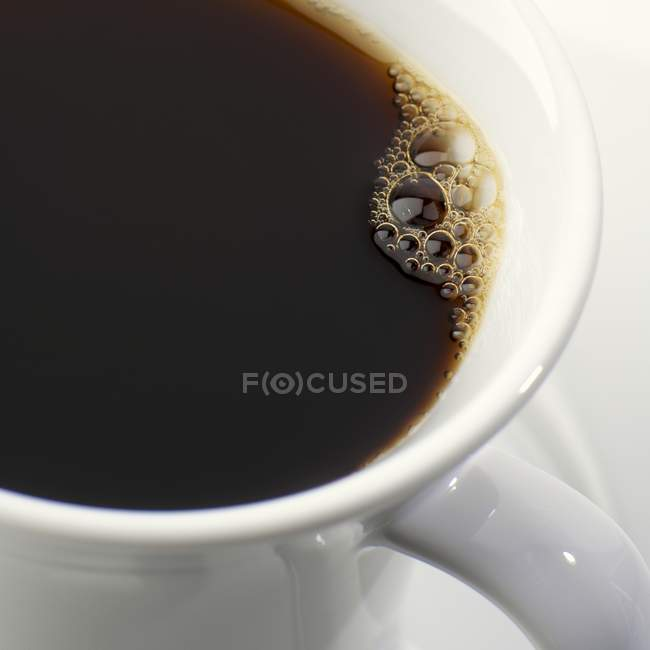 Black coffee with bubbles — Stock Photo