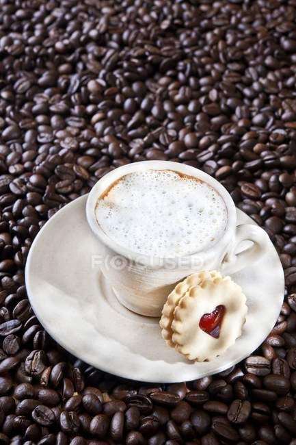 Чашка капучино на кофейных зерен — стоковое фото