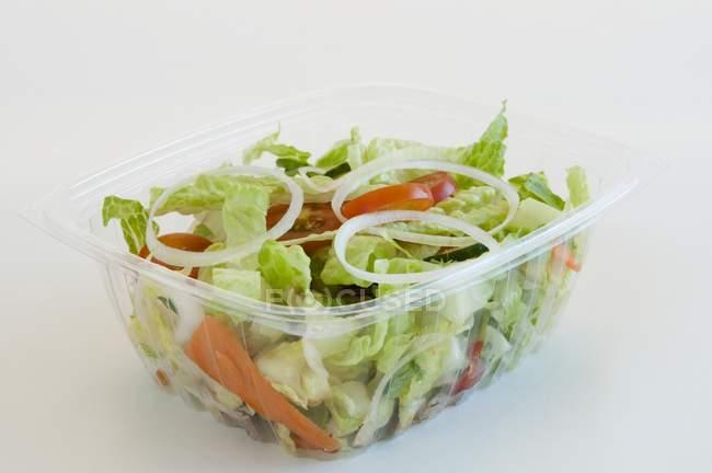 Садові салат в пластиковому контейнері To Go над білим тлом — стокове фото