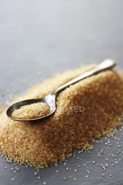 Teaspoon on pile of brown sugar — Stock Photo