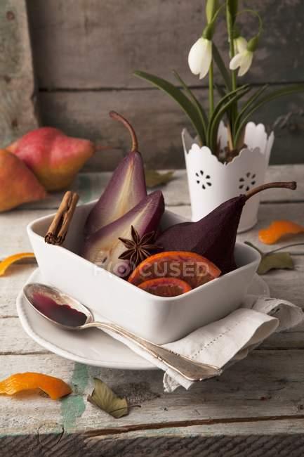 Nahaufnahme von Birnen in Rotwein mit Orangenscheiben und Gewürzen — Stockfoto