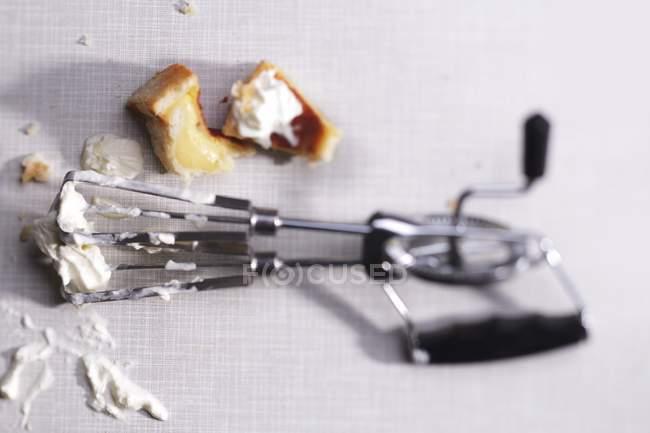 Вид зверху крему залишається на ручної міксер та тісто штук — стокове фото