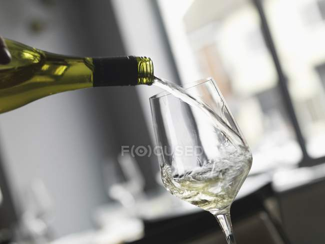Verser le vin blanc en verre — Photo de stock