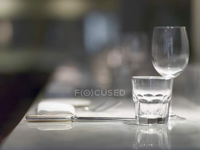 Closeup view of a place setting with glasses, cutlery and a napkin — Stock Photo