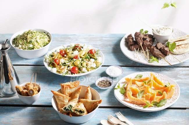 Vista de cerca de varios platos veraniegos en la mesa de madera - foto de stock