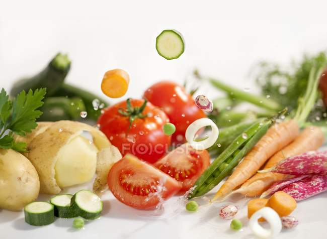 Ingredients for vegetable soup laying on white surface — Stock Photo