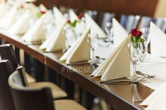 Uma tabela descontraída com guardanapos dobrados e rosas — Fotografia de Stock