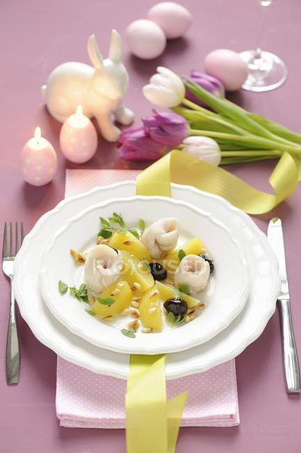 Steamed zander rolls with potatoes, olives and pine nuts for Easter on white plate over towel — Stock Photo