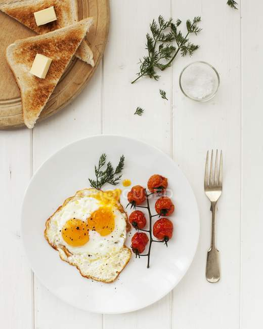 Fried egg with tomatoes on plate — Stock Photo