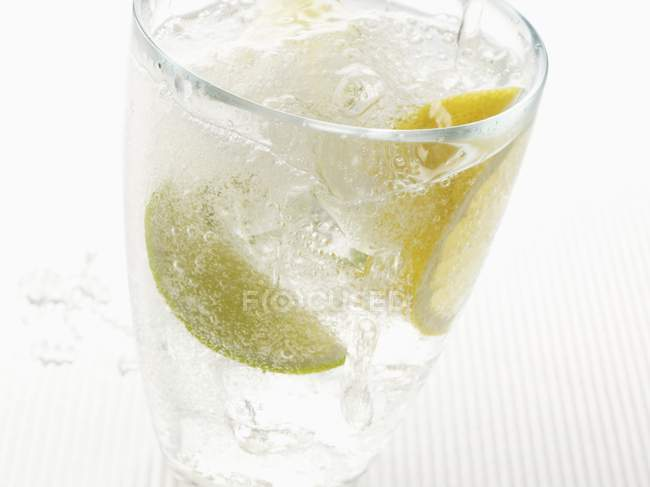 Closeup view of fizzy drink with slices of citrus fruit — Stock Photo