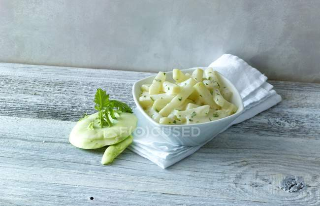 Kohlrabi in a creamy sauce  over wooden surface — Stock Photo