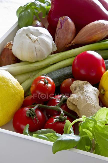 An arrangement of various types of vegetables in a white wooden crate — Stock Photo