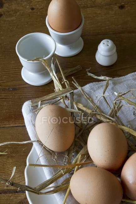 Closeup view of brown eggs with straw on a plate and in egg cups — Stock Photo