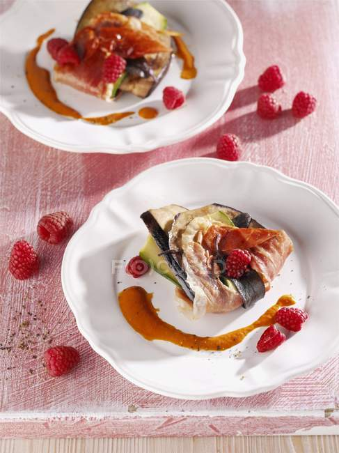 Aubergine and courgette saltimbocca with raspberries on white plate — Stock Photo