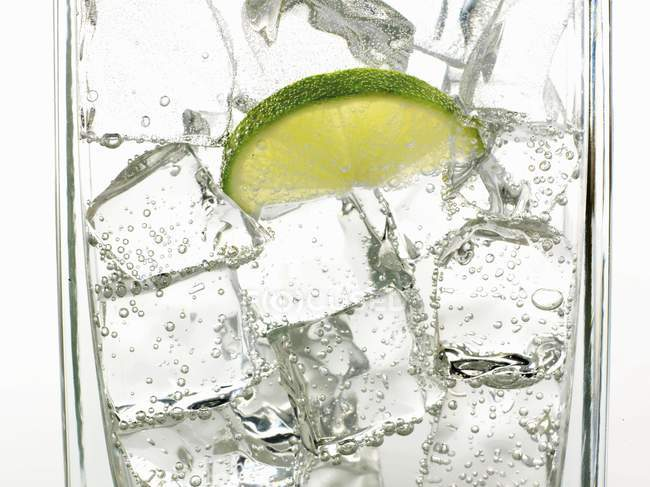 Closeup view of mineral water with ice cubes and slice of lime — Stock Photo