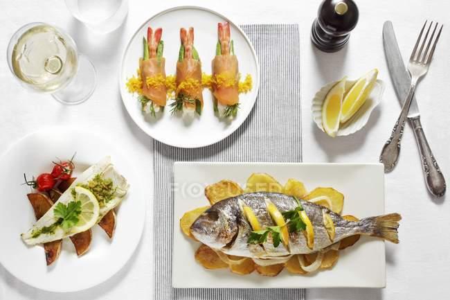 Tres platos de pescado diferentes con limones y vino blanco en platos blancos sobre la mesa - foto de stock