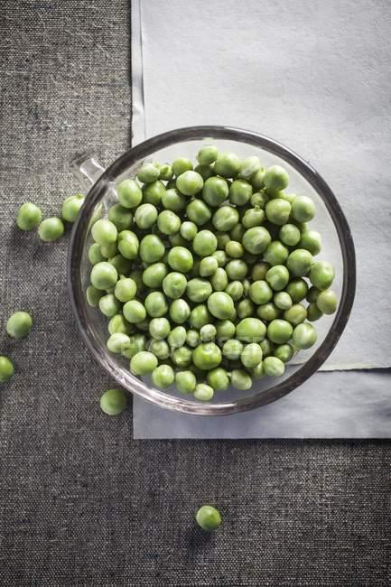 Fresh peas in glass bowl — Stock Photo