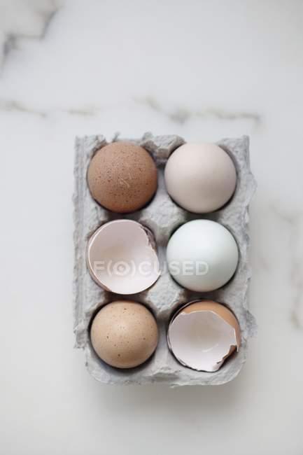 Цельные яйца и яичная скорлупа в коробке — стоковое фото